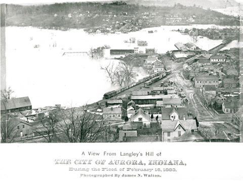 Black and white photograph showing a flooded town; caption reads: 'A View From Langley's Hill of The City of Aurora, Indiana, during the Flood of February 16, 1883. Photographed by James N. Walton.'