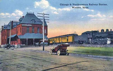 Colorized photo postcard of a red brick train station next to railroad tracks on which a grey steam engine pulling orange cars stands; a violet motorcar, circa 1910, stands on the street outside the station