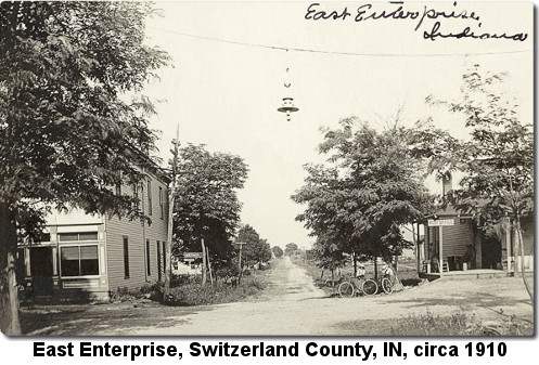 Black and white photograph showing a dirt road running off into the distance and an intersection in the foreground with a house on the left and a Post Office on the right; caption reads: 'East Enterprise, Switzerland County, IN, circa 1910'