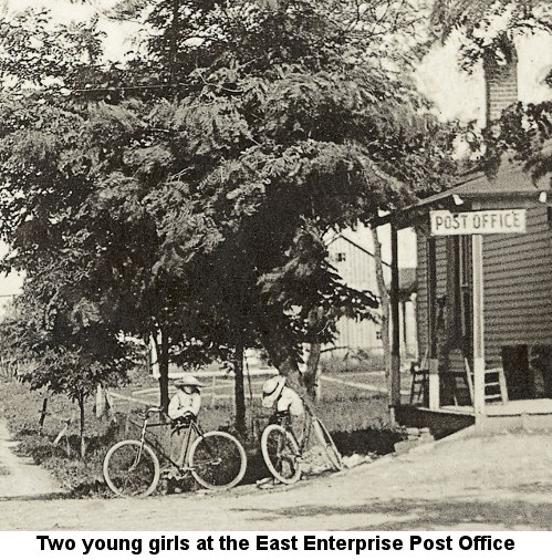 Black and white photograph showing two young girls in long skirts and broad straw hats standing with their fat-tired bicycles to the left of the porch of a building, from whose roof hangs a wooden sign reading 'POST OFFICE'; caption reads: 'Two young girls at the East Enterprise Post Office'