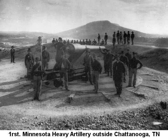 1rst. Minnesota Heavy Artillery outside Chattanooga, TN; photograph showing several soldiers standing around a large cannon on a stationary mount with a view of a town, river and high hill behind them
