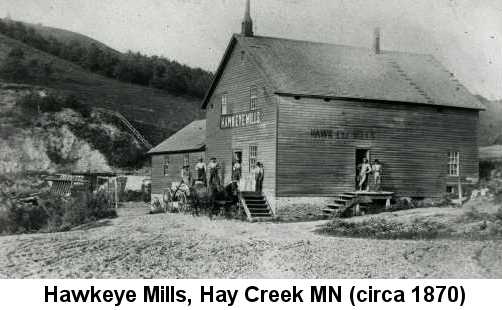 Hawkeye Mills, Hay Creek, MN (circa 1870); black and white photo of a frame mill building with several people standing on its two porches, and wooded hills in the background