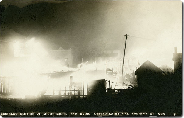 Black and white photograph at night showing several two-story wooden storefronts in flames next to a leaning telephone pole, with smaller black buildings silhouetted in the foreground