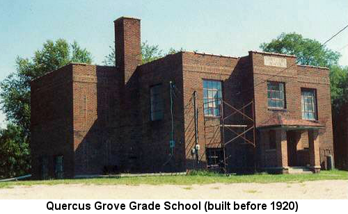 Color photograph of an unused, small, 2-story red brick flat-roofed school building