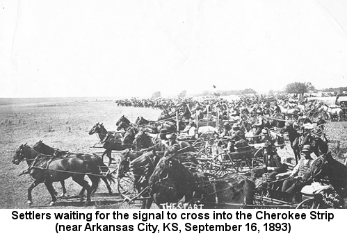 Black and white photograph of a crowd of mostly men on horseback and in wagons, waiting to the right of an invisible line; caption reads: 'Settlers waiting for the signal to cross into the Cherokee Strip (near Arkansas City, KS, September 16, 1893)'