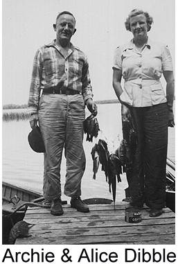 Black and white photograph of Archie and Alice Dibble standing on a dock at a lake, holding a string of fish