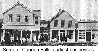 Black and white photo of several frame store-front buildings along a dirt street--some of the first businesses in Cannon Falls