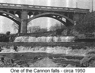 Black and white photo of two tiers of low waterfalls, in front of a bridge--one of the Cannon falls, circa 1950