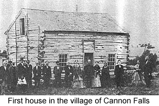 Black and white photo of a rough frame cabin, before which stand several men and women in mid-19th. century clothing--the first house in the village of Cannon Falls