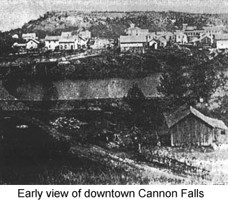 Black and white photo showing houses and stores on a low bluff across a river--early view of downtown Cannon Falls