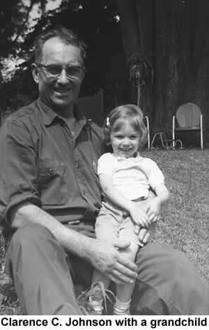 Black and white photo of Clarence C. Johnson, seated, holding a grandaughter