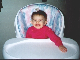 Picture of Emily sitting at a high chair and grinning exhuberantly