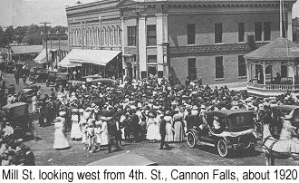 Black and white  photograph of Mill St. looking west from 4th. St., Cannon Falls, about 1920, showing buildings presumably owned by Dick Dibble, with a crowd of people celebrating a patriotic holiday
