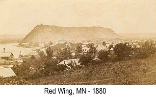 Sepia-tint wide-angle photo of the city of Red Wing, MN in 1880, showing Barn Bluff in the background