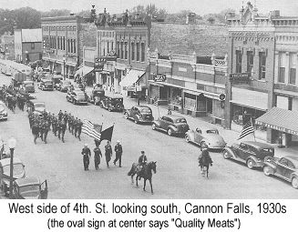 Black and white  photograph of the west side of 4th. St. Cannon Falls, looking north, in the 1930s; an oval sign over a one-story shop about halfway up the street says 'Quality Meats'